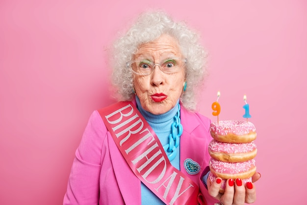 Senior femme aux cheveux gris ridée célèbre son 91e anniversaire détient des beignets avec des bougies costume élégant et ruban
