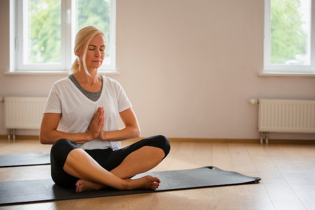 Senior femme blonde pratiquant le yoga