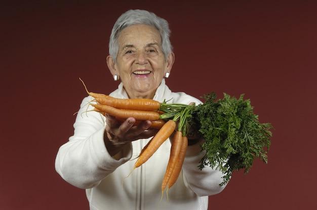 Senior femme avec des carottes