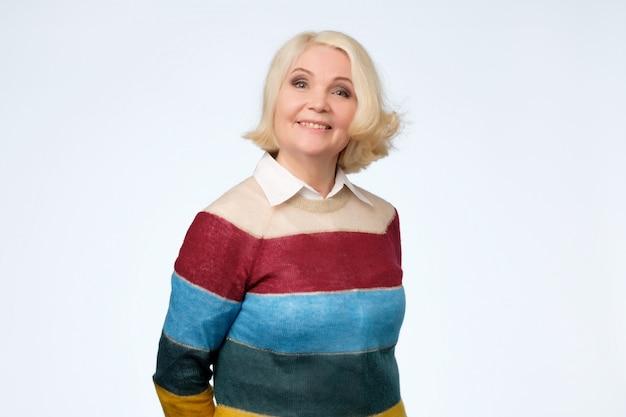 Senior femme caucasienne aux cheveux blonds en pull coloré souriant