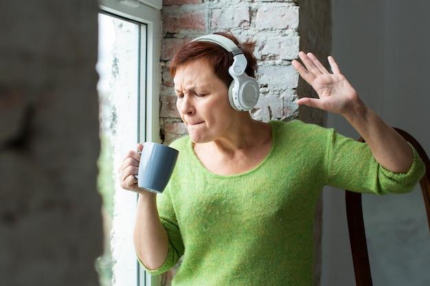 Senior femme chantant à la tasse de café