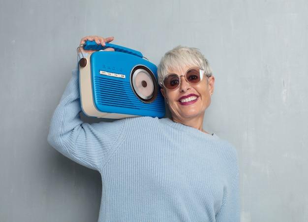Senior femme cool avec une radio vintage, écouter de la musique contre