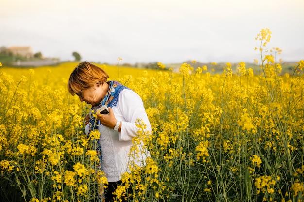Senior femme dans un champ de fleurs jaunes