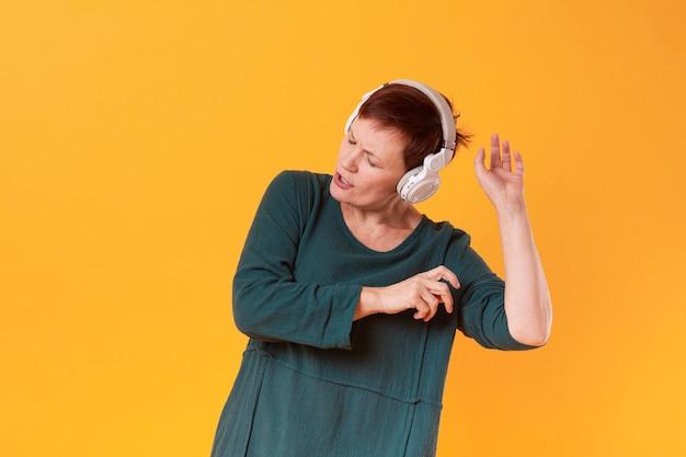 Senior femme danser et écouter de la musique
