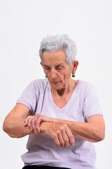 Senior femme avec douleur au poignet sur fond blanc