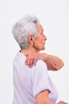 Senior femme avec douleur à l'épaule sur fond blanc