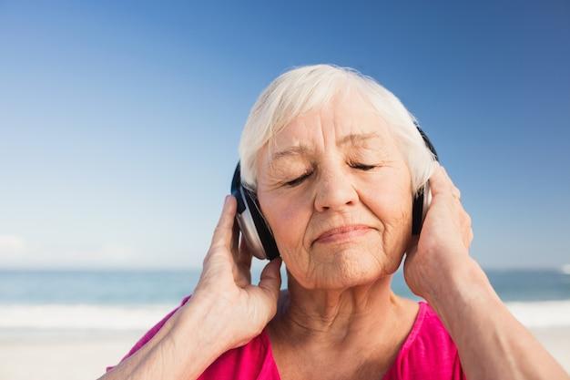 Senior femme écoutant de la musique avec un casque