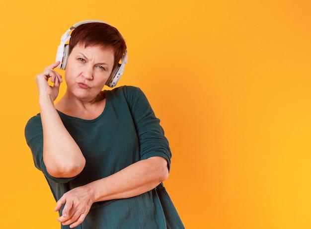 Senior femme écoutant de la musique et regardant un photographe
