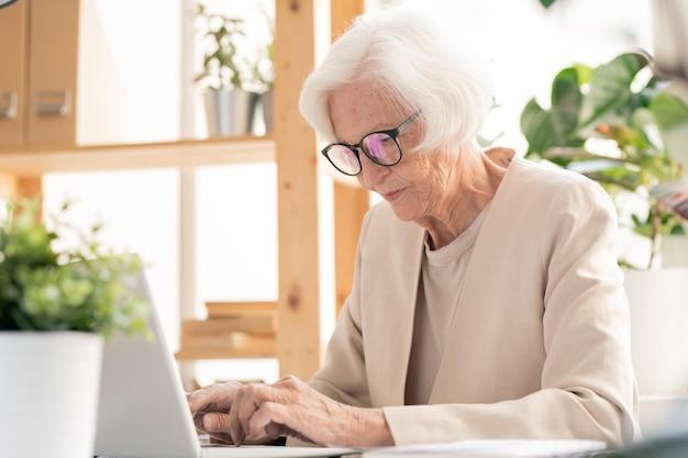 Senior femme élégante occupée en costume blanc et lunettes tapant sur le clavier de l'ordinateur portable tout en naviguant sur le net par 24