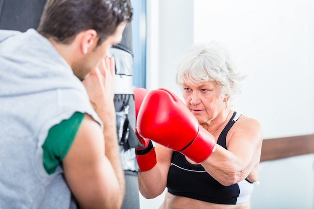 Senior femme avec entraîneur en boxe sparring