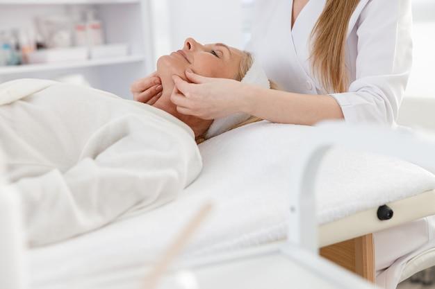 Senior femme est allongée sur le dos, se fait masser le visage. soin de beauté de massage du visage.