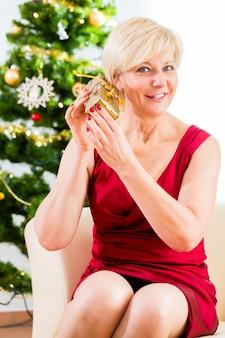 Senior femme est curieuse de savoir cadeau de noël