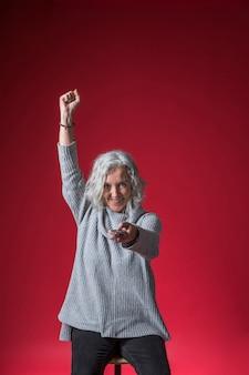 Senior femme excitée, changer de chaîne avec télécommande acclamant sur fond rouge