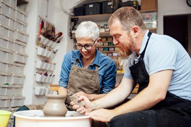 Senior femme faisant tourner l'argile sur une roue avec un enseignant à la classe de poterie