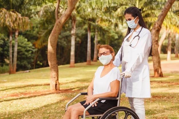 Senior femme handicapée avec soignant dans le jardin de la maison de soins infirmiers