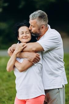 Senior femme et homme debout et étreignant en plein air, homme embrassant une femme. rapports. verticale