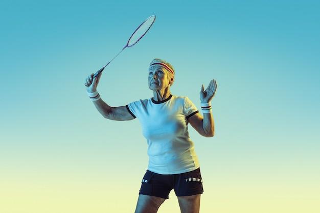 Senior femme jouant au badminton en vêtements de sport sur gradient en néon