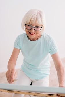 Senior femme joyeuse dans des verres avec des cheveux gris dessin au crayon art de la créativité nature morte