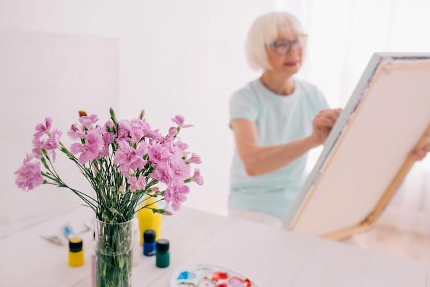 Senior femme joyeuse dans des verres avec des cheveux gris peinture still life créativité art hobby