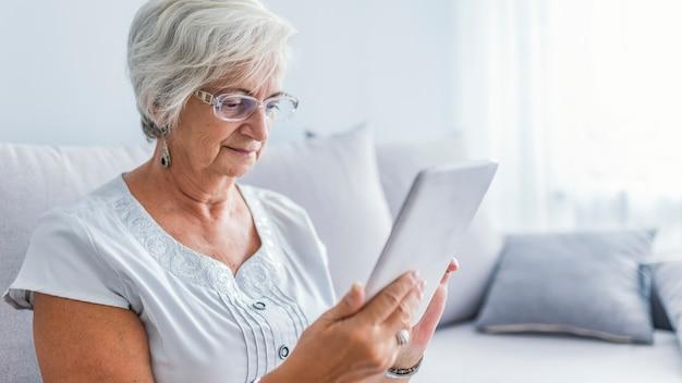 Senior femme avec des lunettes de navigation sur tablette numérique
