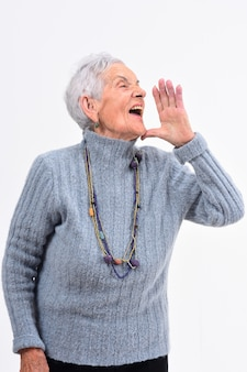 Senior femme mettant une main dans la bouche et crie sur fond blanc