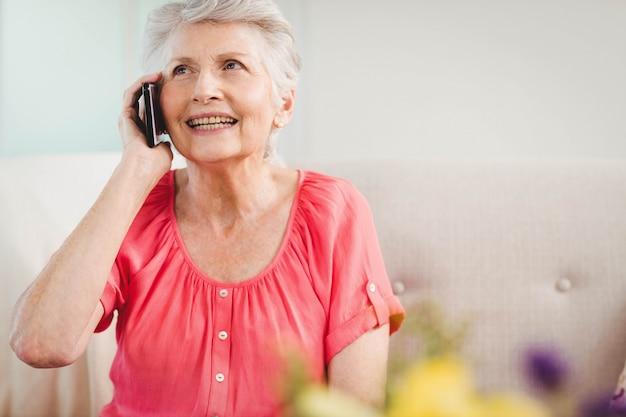 Senior femme parlant au téléphone dans le salon