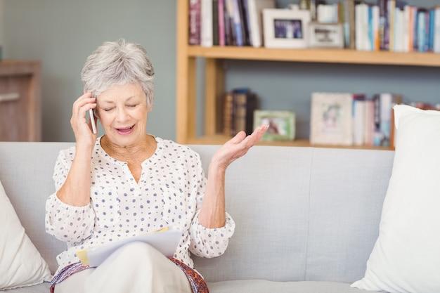 Senior femme parlant sur un téléphone mobile tout en regardant les documents