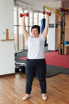 Senior femme avec des poids