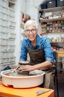 Senior femme potier travaillant sur le tour de potier assis dans son atelier