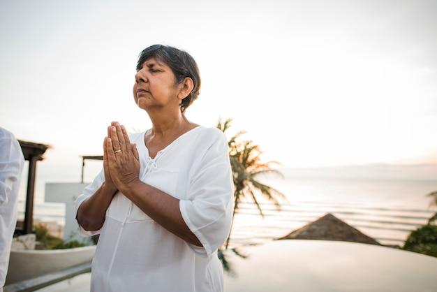 Senior femme pratiquant le yoga le matin