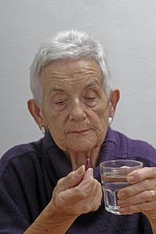 Senior femme prenant des pilules