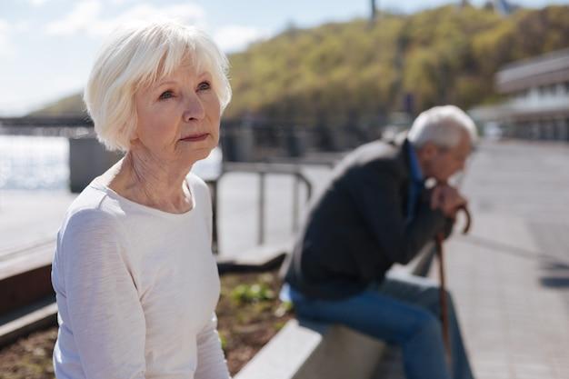 Senior femme réfléchie élégante regardant le ciel et assis à l'extérieur alors que l'homme âgé réfléchit à ses problèmes