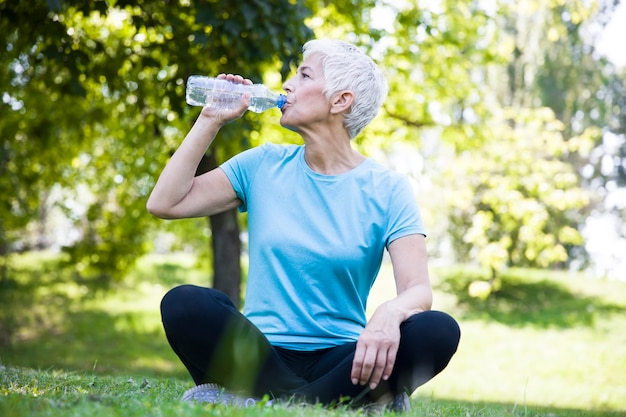 Senior femme resing et eau potable après l'entraînement dans le parc