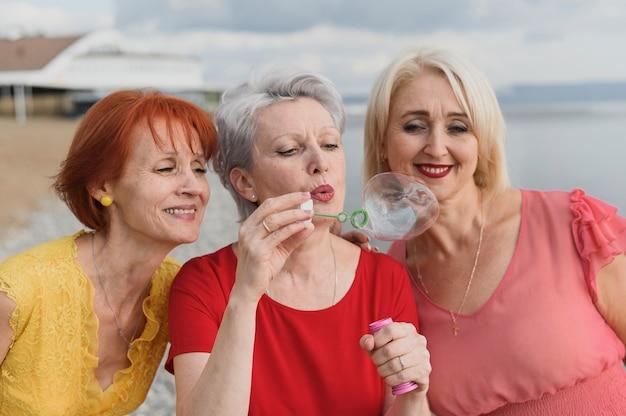 Senior femme soufflant des bulles