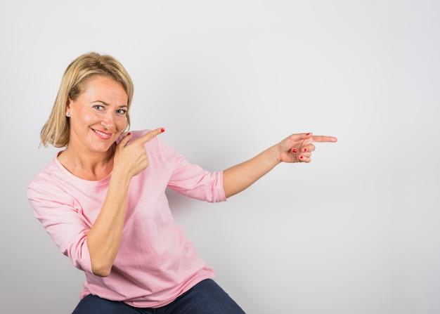 Senior femme souriante en chemisier rose pointant sur le côté