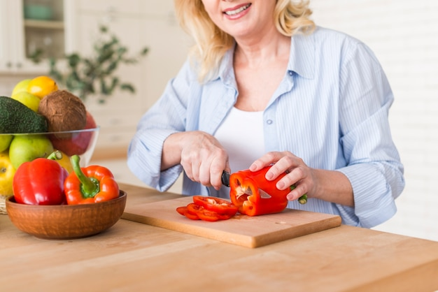 Senior femme souriante coupe le poivron rouge avec un couteau