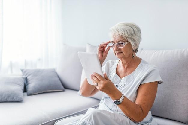 Senior femme avec tablette assis sur un canapé dans le salon