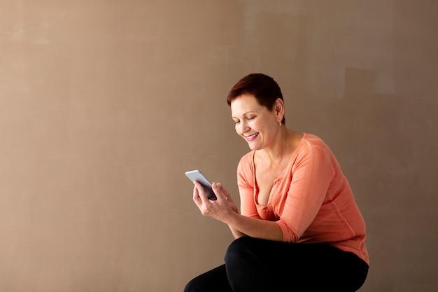 Senior femme avec téléphone souriant