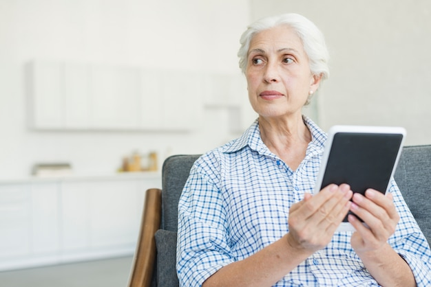 Senior femme tenant une tablette numérique à la recherche de suite