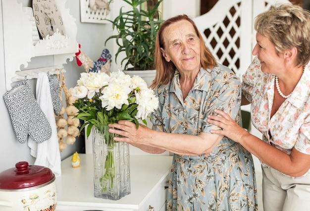 Senior femme tenant un vase de fleurs blanches se tenant près de sa fille