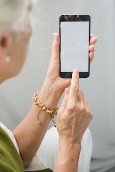 Senior femme touchant l'écran d'affichage mobile