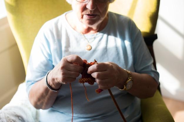 Senior femme tricot pour passe-temps à la maison