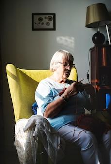Senior femme tricotant à la maison