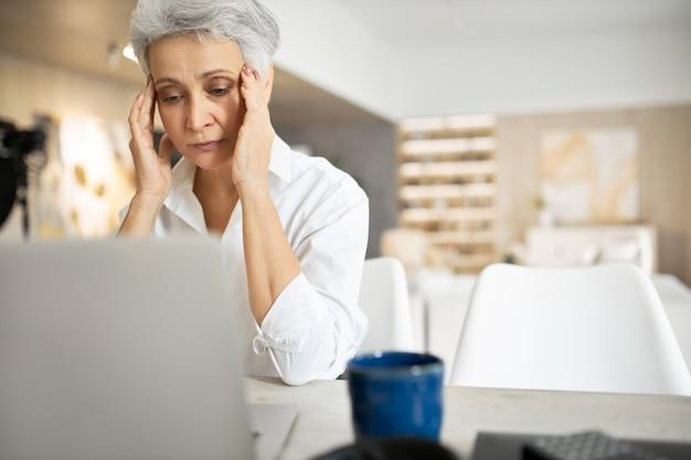 Senior femme triste aux cheveux gris travaillant sur un ordinateur portable, se frottant les yeux ou cachant des larmes, plein de pensées agitées