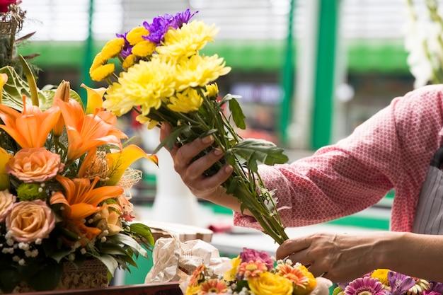 Senior femme vend des fleurs sur le marché aux fleurs local