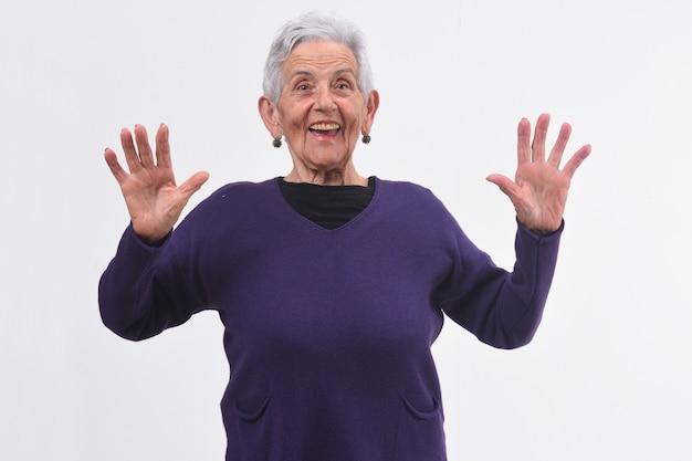 Senior femme avec un visage surpris et mains surélevées sur fond blanc
