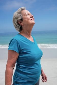 Senior femme avec des yeux fermés debout sur la plage