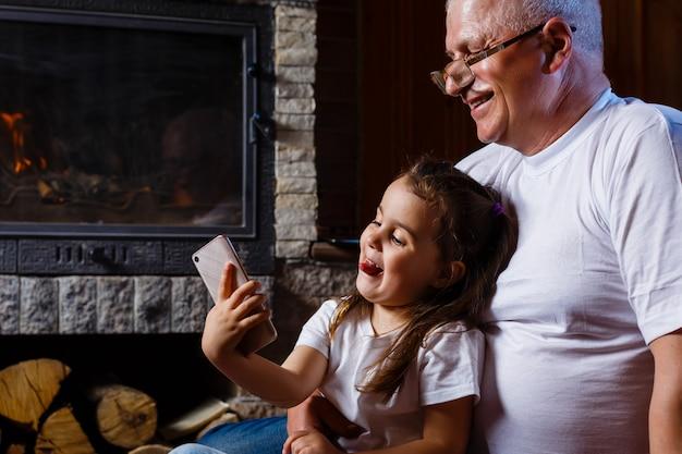 Senior grand-père et petite-fille en vedette sur les smartphones à l'intérieur
