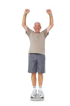 Senior homme acclamant sur une échelle de poids