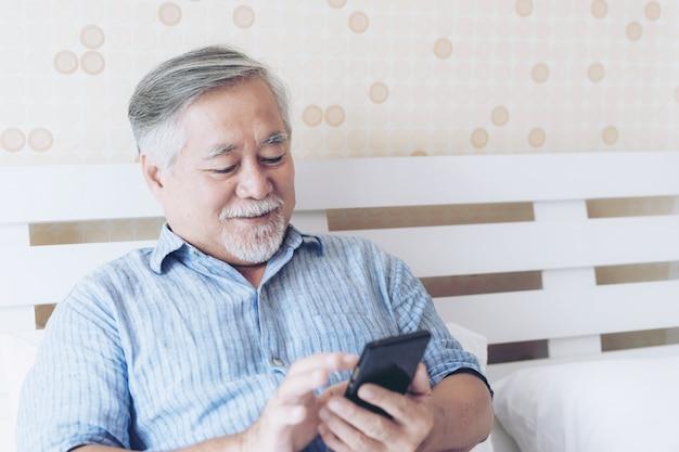 Senior homme à l'aide d'un smartphone, souriant se sentir heureux au lit à la maison - concept senior lifestyle